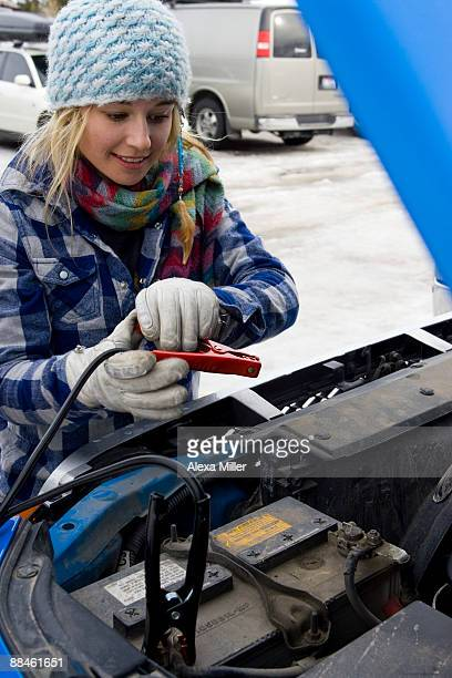 Young woman recharging dead car battery.