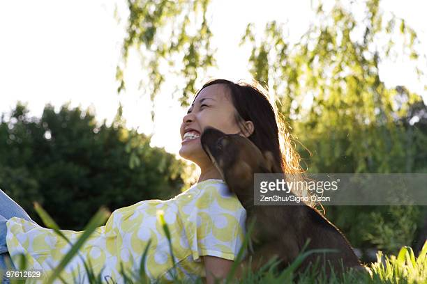 Young woman reclining in grass with puppy, laughing