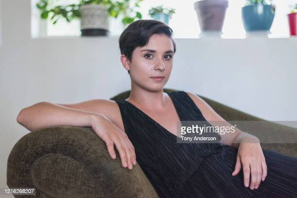 young woman reclining on sofa in her home - v neck stock pictures, royalty-free photos & images