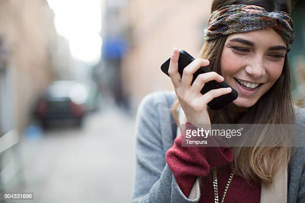 Young woman recording a voice message with a smart phone.