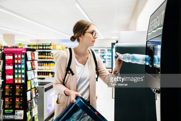 young woman recycling bottles at the supermarket - recycling stock pictures, royalty-free photos & images