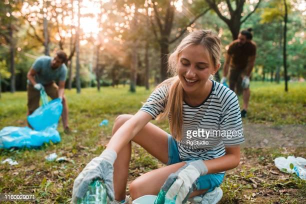 jonge vrouw recycling flessen - verzameling stockfoto's en -beelden