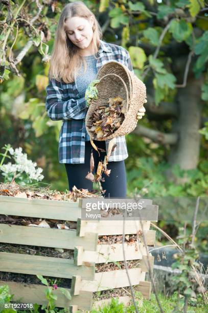 Young Woman Recycling Dried Leaves in the Composter, Slovenia, Europe
