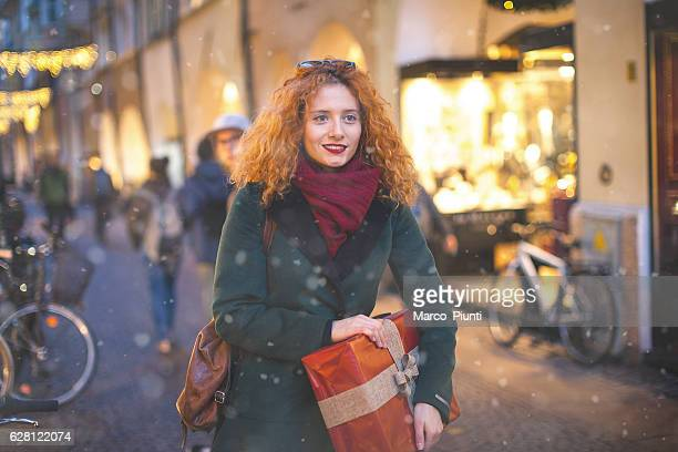 Young woman redhead in the city with gift