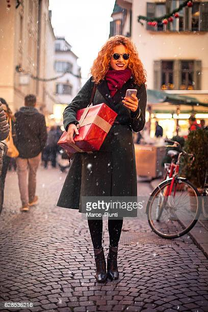Young woman redhead using smartphone in the city with gift