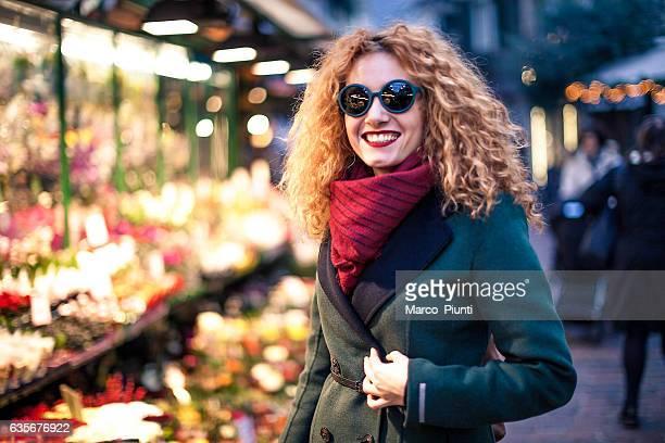 Young woman redhead walking through citylight