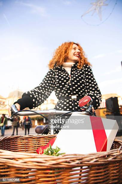 Young woman redhead with bike and gift