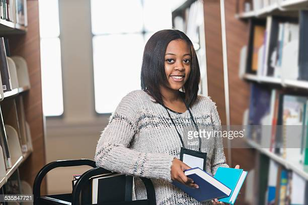 young woman refiling books on library shelf - part time job stock pictures, royalty-free photos & images