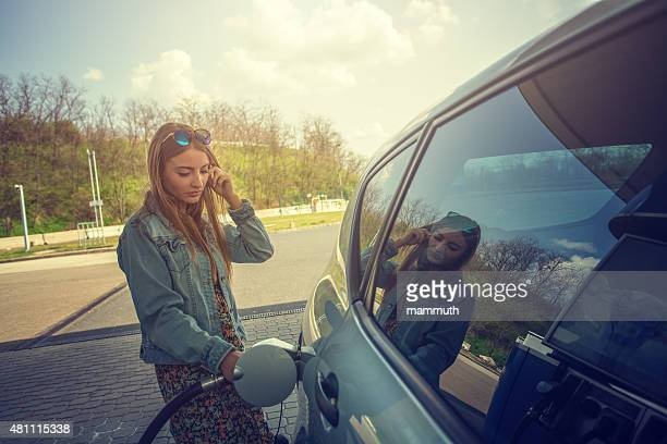 young woman refilling car with fuel - gas tank stock photos and pictures