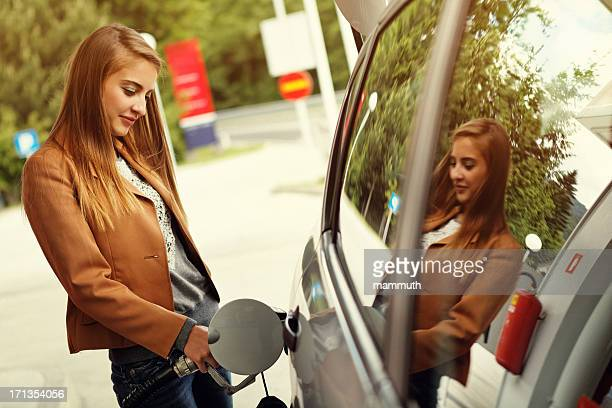 young woman refilling car with gas pump - refuelling stock pictures, royalty-free photos & images