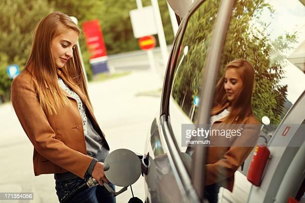 Junge Frau unbegrenzt Auto mit gas pump