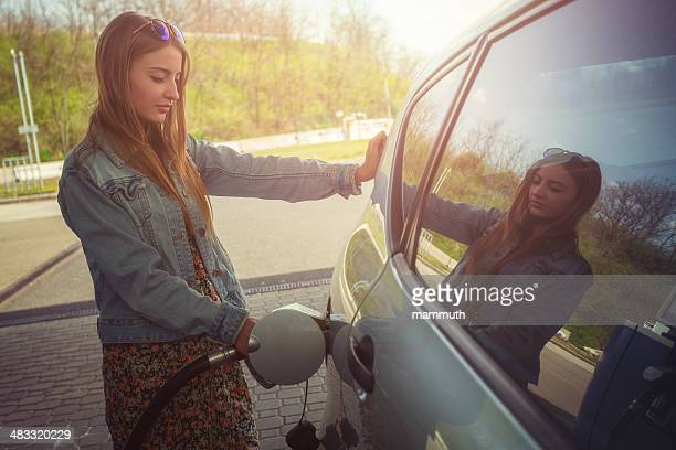 young woman refilling car with gas pump - gas tank stock photos and pictures