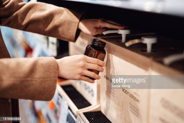 young woman refilling shower gel into a reusable glass bottle in zero waste store - sustainable lifestyle stock pictures, royalty-free photos & images