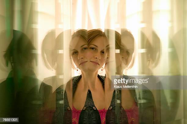 young woman reflected in glass panes - repetitie stockfoto's en -beelden