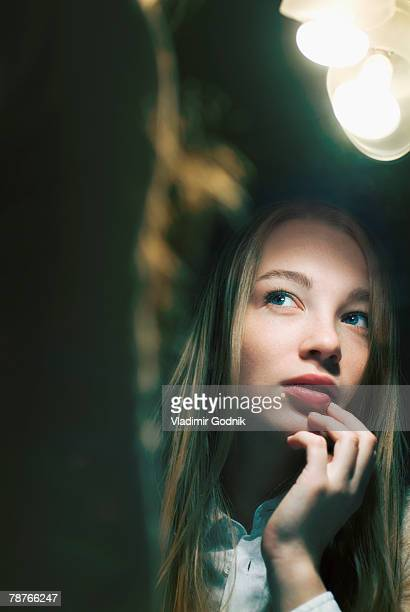 Young woman reflected in mirror looking away