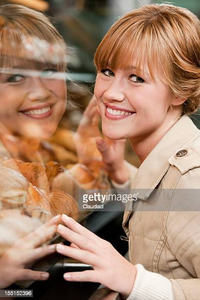 Young woman reflecting in window of a bakery
