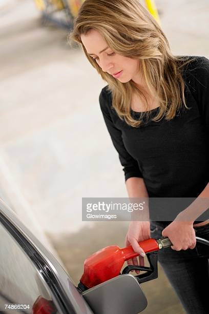 Young woman refueling a car