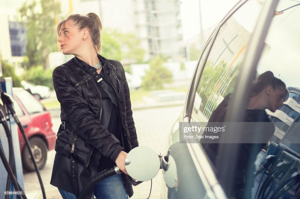 Young woman refueling her car : Stock Photo