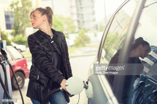 Young woman refueling her car