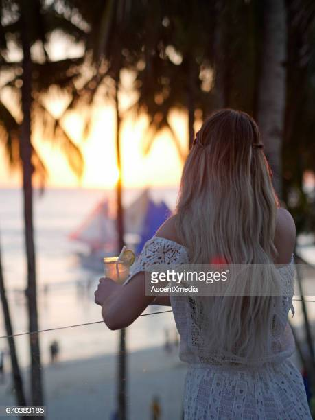 Young woman relaxes above beach with cocktail
