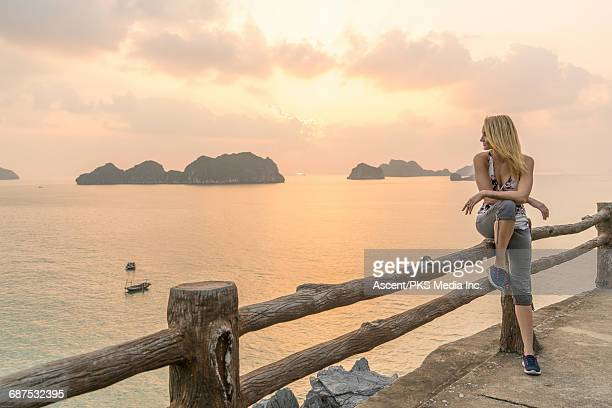 young woman relaxes at sunrise, enjoys sea view - plus fours stock photos and pictures