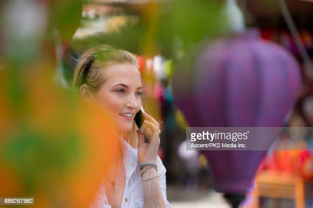 Young woman relaxes by Asian umbrellas, talks on phone