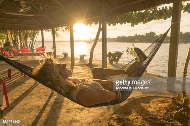 Young woman relaxes in hammock, in resort setting