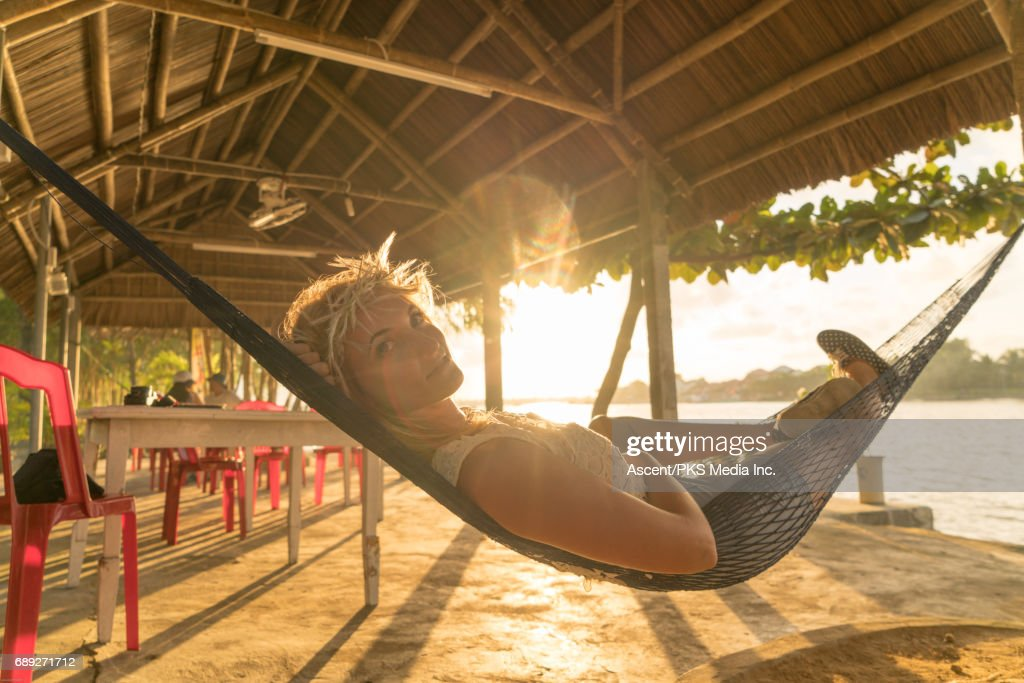 Young woman relaxes in hammock, in resort setting : Stock Photo
