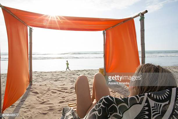 Young woman relaxes in shade on beach at sunrise