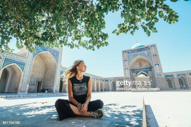 Young woman relaxes in tranquil grounds of mosque