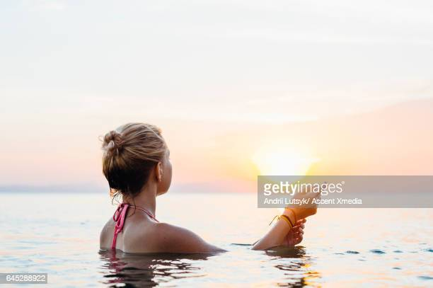 Young woman relaxes in tropical lagoon,sunset