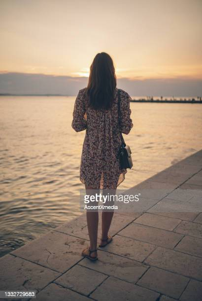 young woman relaxes near lakeshore at sunrise - shallow stock pictures, royalty-free photos & images