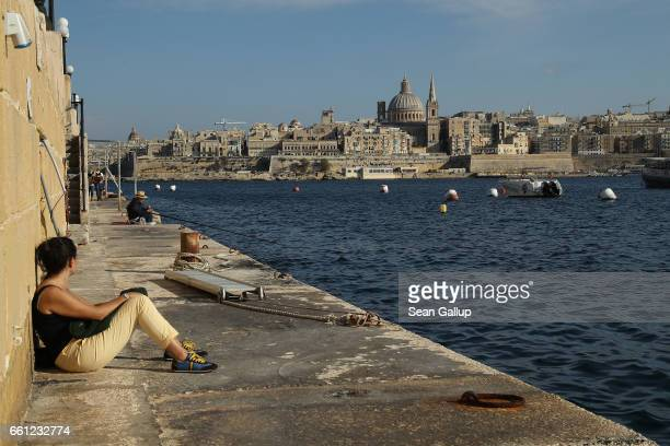 A young woman relaxes on a bay as Valletta including the dome of the Basilica of Our Lady of Mount Carmel stands behind on March 29 2017 in Sliema...