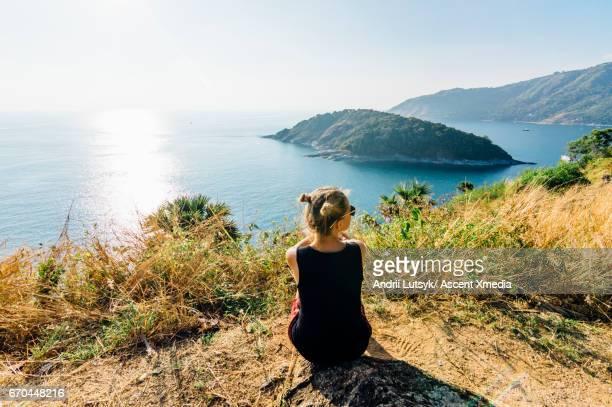 young woman relaxes, on hillside above sea - isla mujeres fotografías e imágenes de stock