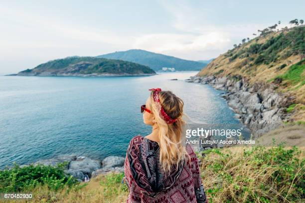 Young woman relaxes, on hillside above sea