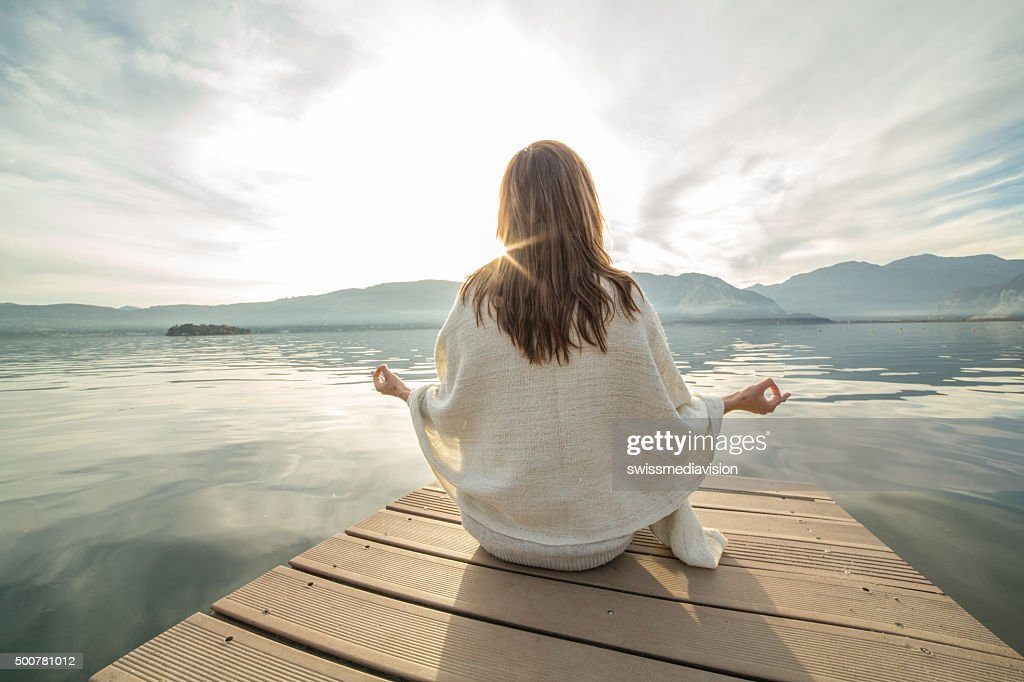 Young woman relaxes on lake pier, exercises yoga : Stock Photo