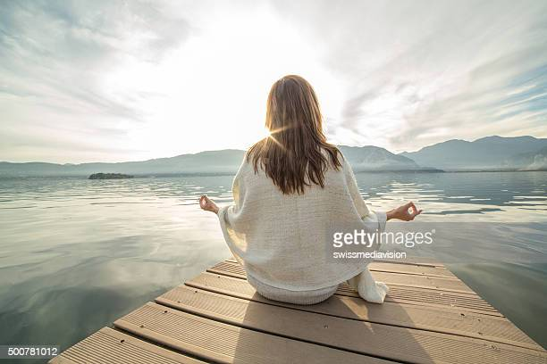 Young woman relaxes on lake pier, exercises yoga