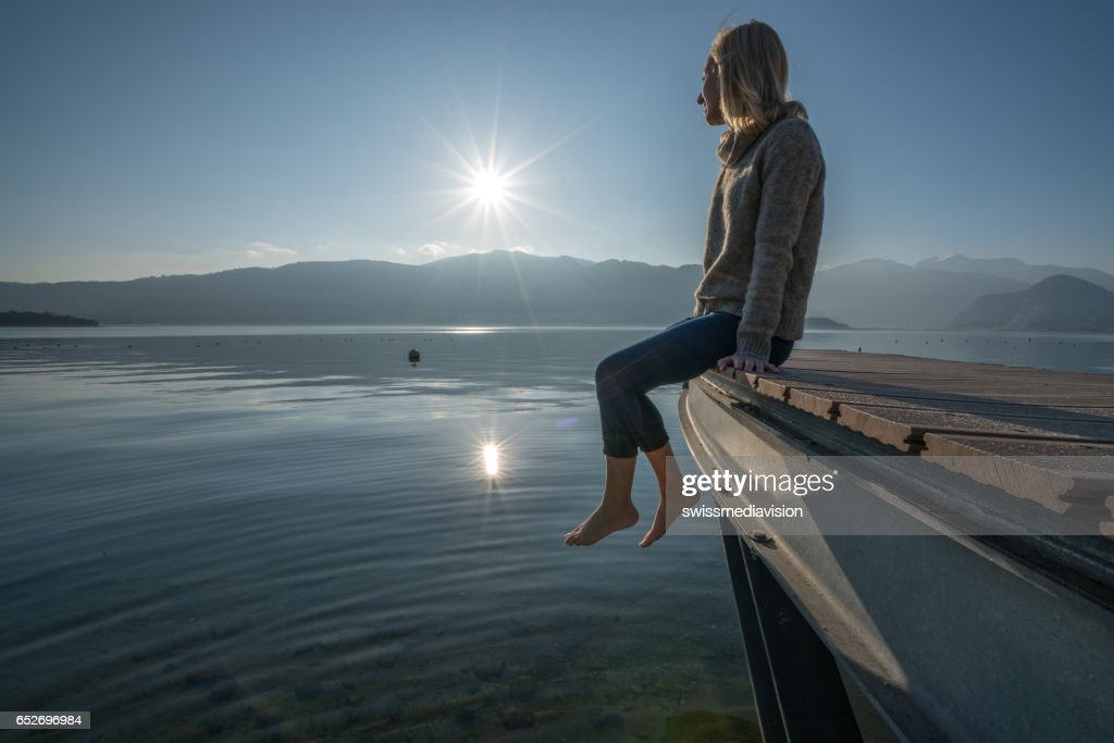 Young woman relaxes on lake pier, watches sunset : Stock Photo