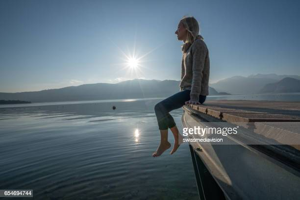 Young woman relaxes on lake pier, watches sunset