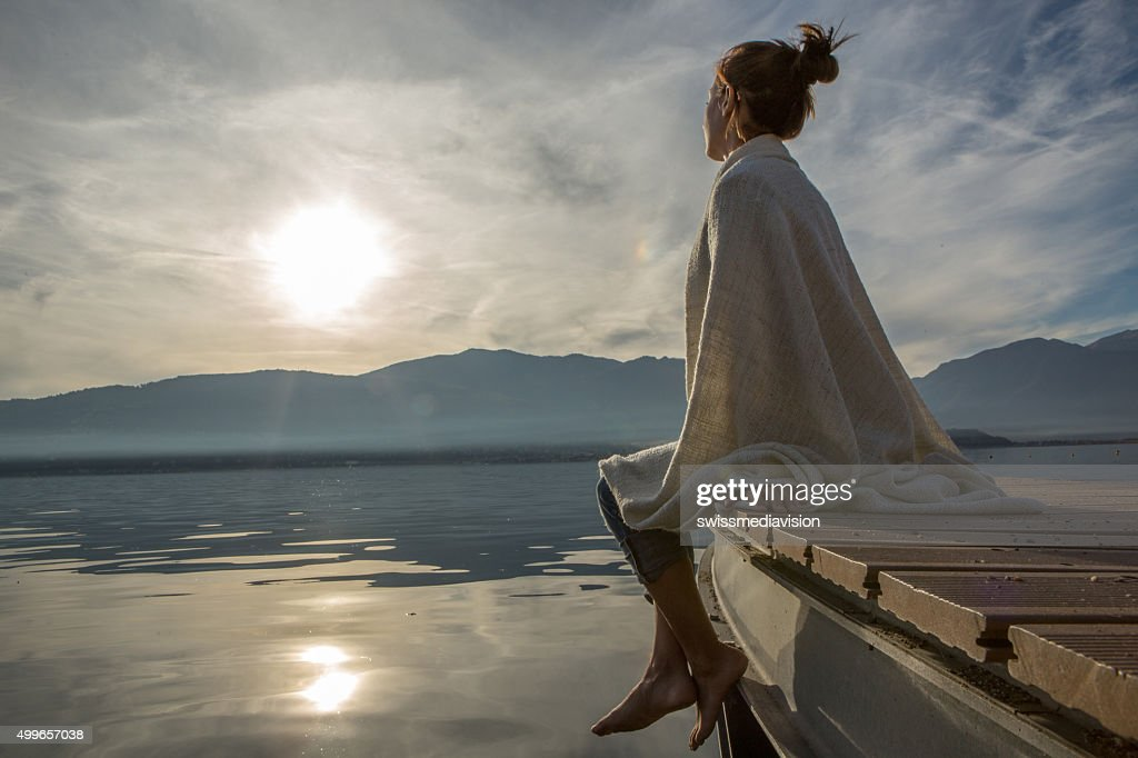 Young woman relaxes on lake pier with blanket, watches sunset : Stock Photo
