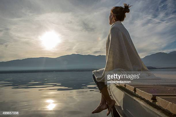 young woman relaxes on lake pier with blanket, watches sunset - kalmte stockfoto's en -beelden