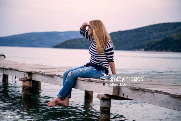 Young woman relaxes on pier