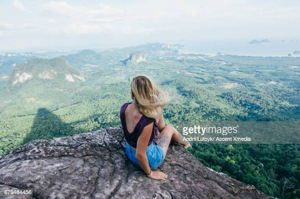 Young woman relaxes on rock platform above valley
