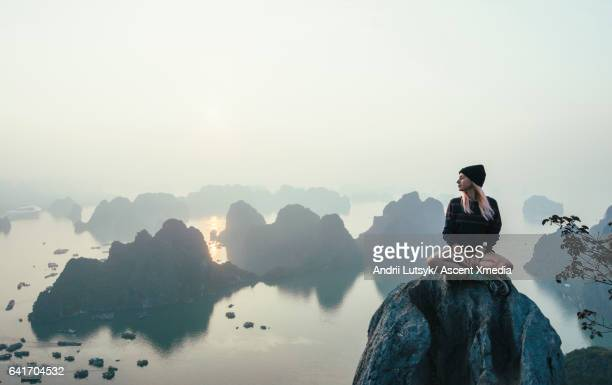 Young woman relaxes on rock summit, looks over sea