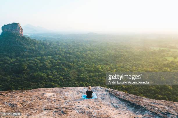 young woman relaxes on rocky crest above jungle, sunrise - sri lanka stock pictures, royalty-free photos & images