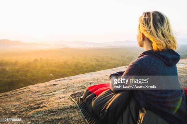 Young woman relaxes on rocky crest above jungle, sunrise