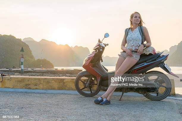 Young woman relaxes on scooter, looks off