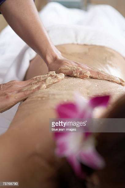 Young woman relaxes on spa massage table as masseuse rubs her back.