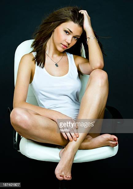 Young Woman Relaxes on White Chair.