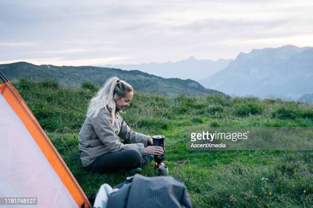 young woman relaxes outside tent at sunrise - only mid adult women stock pictures, royalty-free photos & images